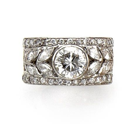 A diamond ring  the wide openwork band centering a round brilliant-cut diamond flanked by marquise-cut diamond four-stone shoulders, all bordered by round brilliant-cut diamonds; central diamond weighing approximately 1.40 carats; remaining diamonds weighing approximately: 1.20 carats total; mounted in platinum