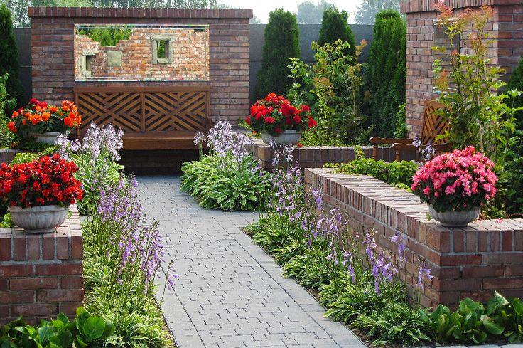 Czerwona cegła w ogrodzie angielskim świetnie komponuje się z zielonymi barwami