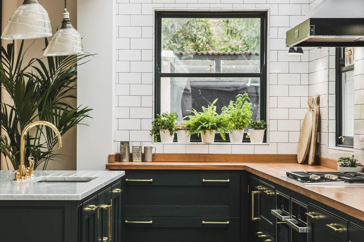 View of an L-shaped kitchen with a central island. The shaker style cabinets with beaded frames are painted in Little Greene Obsidian Green. The handles a brass d-bar style. The worktop on the perimeter units is Iroko wood and Carrara marble on the island. A single sink sits in the island with a polished brass tap. The tiles are flat white metro tiles with a dark grey grout. A Wolf gas hob sits above Neff ovens with a Falcon extractor hood over the hob.