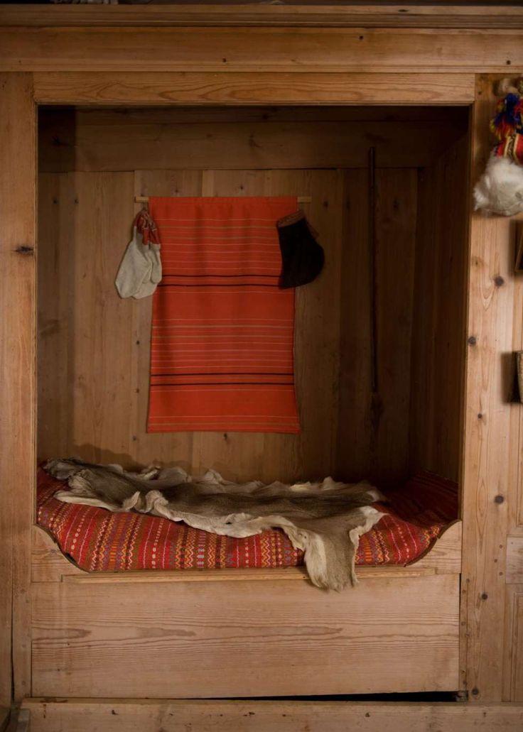 SENG MED SKAP: Den gamle skapsengen med vevd teppe og rådyrskinn står fortsatt der i «Utistuggu». I enden av sengen er det skap med plass til porselen og annet som fulgte med hytta.