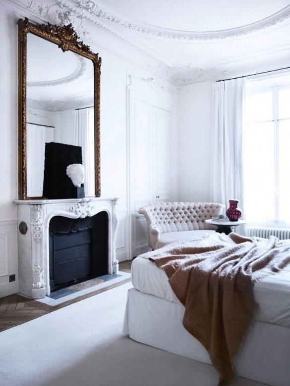 White bedroom with ornate fireplace and large mirror.