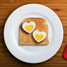 Heart shaped boiled eggs on the toast