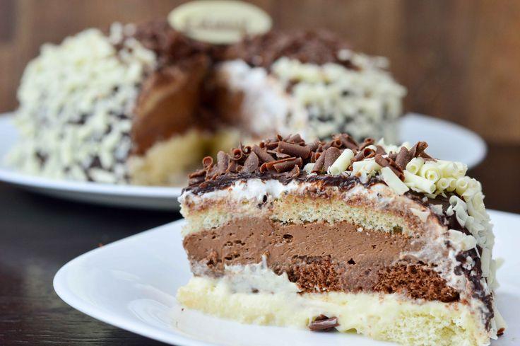 BOLO DOIS AMORES Bolo branco e preto, recheado com creme de chocolate amargo e chocolate branco, coberto com ganache de chocolate meio amargo, decorado com chocolate ralado branco e preto.