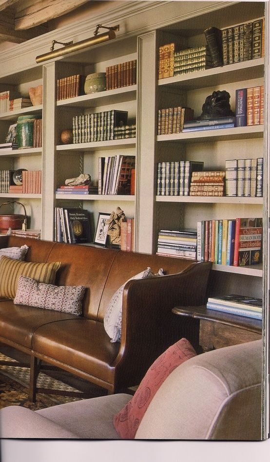 Library with taupe built-in shelves and a cognac colored leather sofa