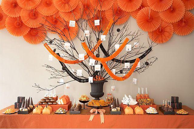 A mesa de doces decoradas nas cores tradicionais do Halloween, preto e laranja.