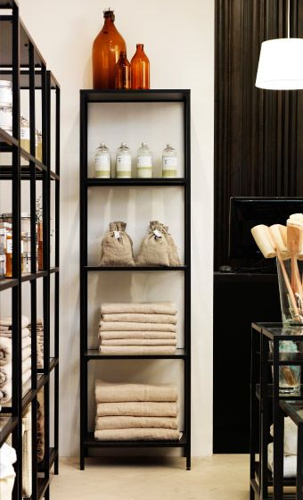 Towels and bottles displayed in VITTSJÖ black shelving unit