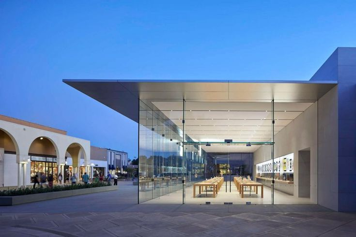 The glass facades of this apple store are designed to make the store feel like part of the plaza in front.