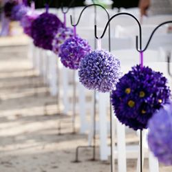 A fun and funky wedding with lots of handmade / DIY details including these purple vari-hued pomanders!