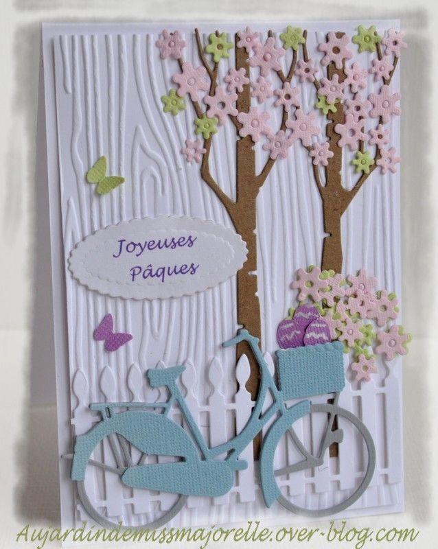 Carte dont le fond est gaufré d'un effet bois et ornée de découpes dont un vélo…
