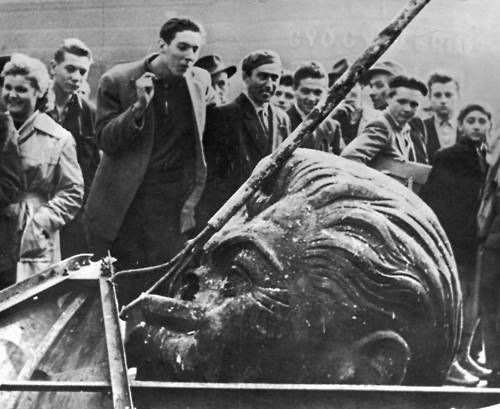 Man spitting on the decapitated head of a statue of Joseph Stalin during the Hungarian Revolt, Budapest Hungary, 1956