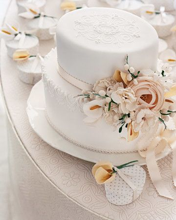 The scale and shape of this cake suggest a gorgeous Victorian hat, so it's appropriate that the decorations adorning it are millinery flowers -- fabric blossoms that are traditionally used by hatmakers. Kromer's royal-icing string work, a stenciled top, and icing flocked with shimmery sanding sugar all add to the romantic feel. Favor boxes, by Denise Sharp, ornamented with fabric calla lilies are covered in custom paper.