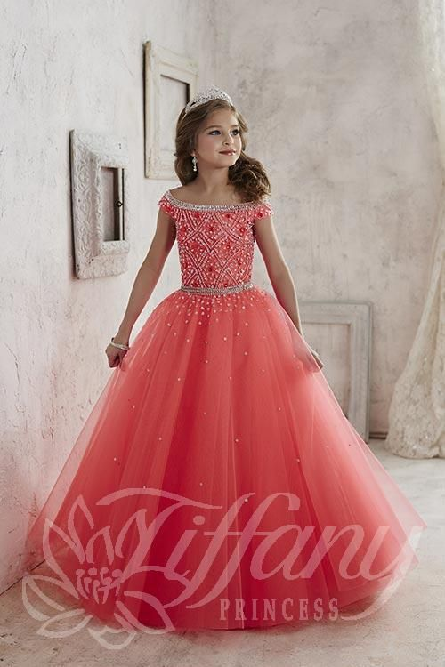 Tiffany style 13458 is breathtaking from head to toe. Off the shoulder neckline with intricate beading pattern on the bodice. Full tulle ballgown skirt with scattered sequins. Lace up corset back. A winning dress!