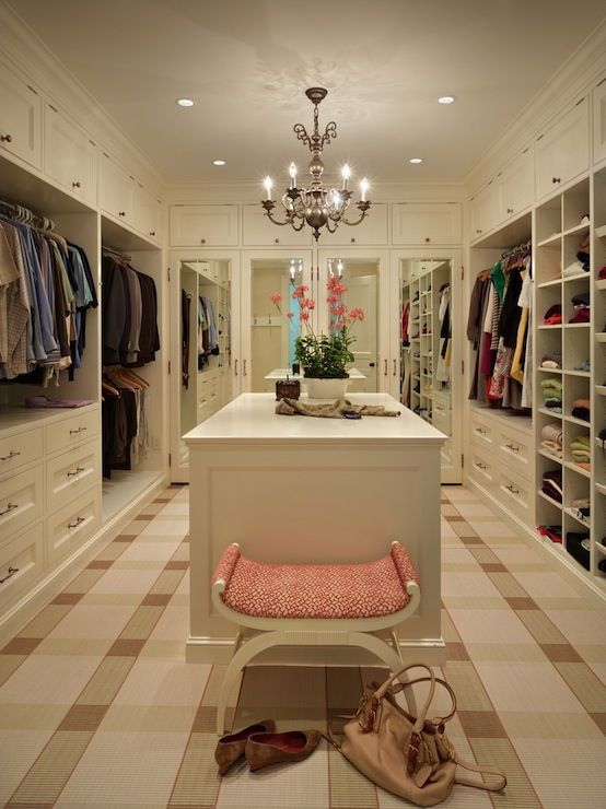 Traditional walk-in closet design with cream built-in cabinets with and mirrored cabinet doors. Closet features chandelier over closet island and ottoman over plaid wall-to-wall carpeting.