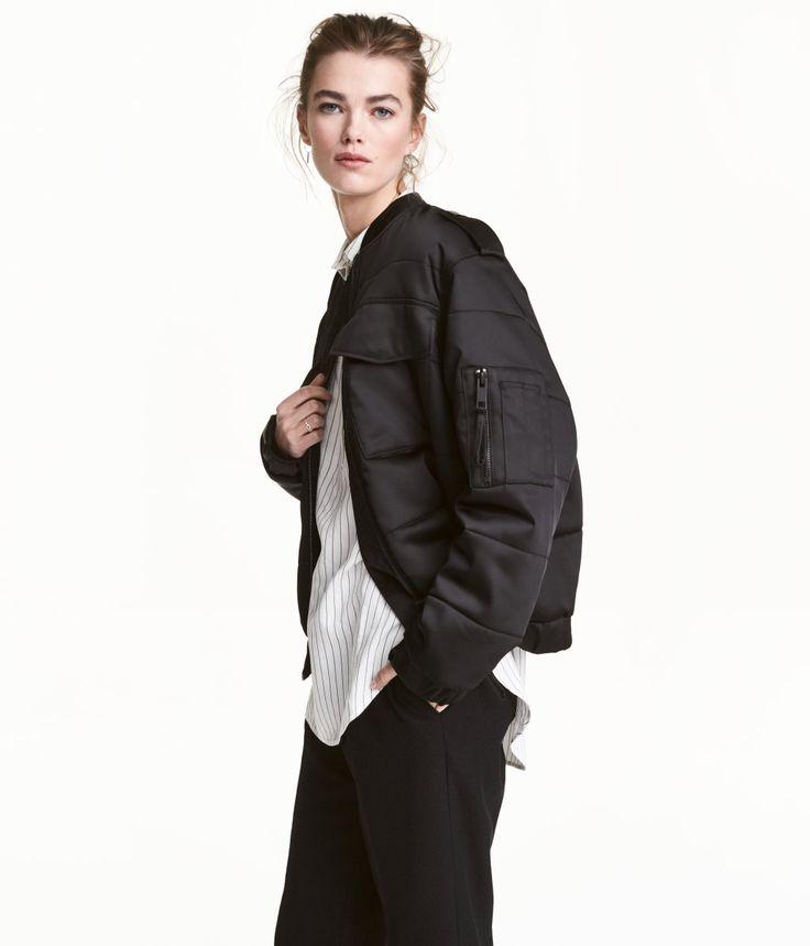 Schwarz. Wattierte Jacke aus leicht glänzendem Webstoff mit Ziernähten. Die Jacke hat einen Stehkragen, Schulterriegel mit Druckknopf und vorn einen