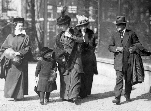 Prinses Juliana bezoekt op ongeveer 5-jarige leeftijd [1914-1915] de dierentuin Artis in Amsterdam. De kleine prinses wordt begeleid haar gouvernante Freule F.L.H. van de Poll (hofdame) en zuster Lena Marting, kinderjuffrouw.