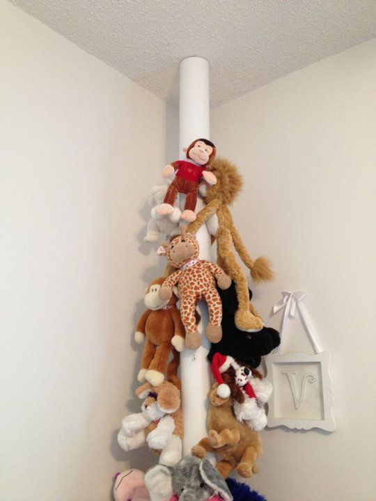 10 Clever Ways to Store Stuffed Animal Collections - Here an Carpet Roll is Recycled with Hooks and Stuffed Animals Perched On!  How Cute!