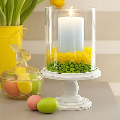"Place a glass hurricane on a plate or pedestal. Center a pillar candle inside it. Fill the surrounding space 1"" high with one color of jellybeans, then add a 1"" layer of a different color directly on top."