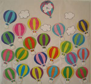 Γράφουμε την τάξη και το τμήμα στο πρώτο αερόστατο, τα ονόματα των παιδιών στα υπόλοιπα και τα εκτυπώνουμε. Όταν τα παιδιά έρχονται στο σχολείο, τοποθετούν τη φωτογραφία τους στο καλάθι του αερόστα…