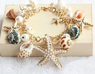 This bracelet has been made by Julyjoy. The details include: a slim chain main with shell, starfish and conch charms, an adjustable length and a lobster clasp fastening.