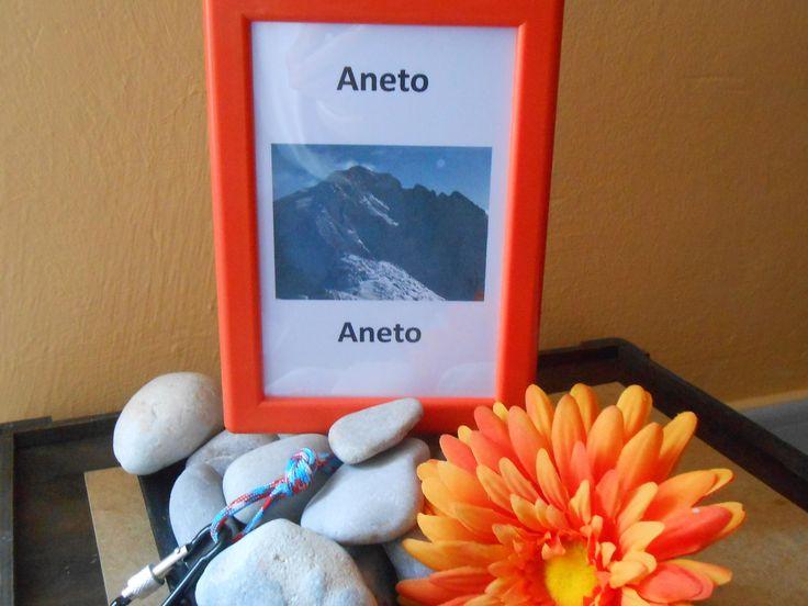 Centre de taula temàtic muntanyes, amb mosquetó, pedres, rètol i flor taronja. www.eventosycompromiso.com