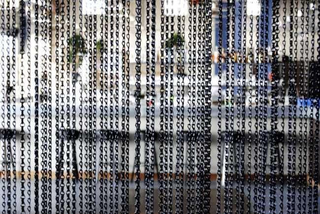 Pro optické rozdělení prostoru využili architekti jemně působící kovové řetízkové záclony.