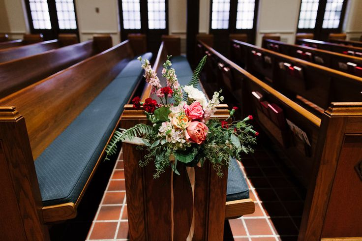 lush pew marker of antique hydrangea, pink and peach roses, pink larkspur, burgundy mini carnations, fern, seeded eucalyptus, and lemon leaf.