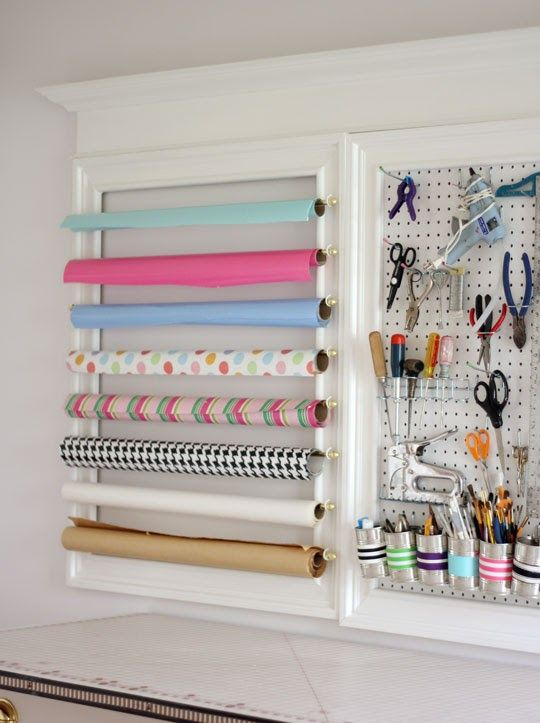 Another use of dowels and hooks to store wrapping paper. I like how she uses a wooden frame to screw the dowels into.
