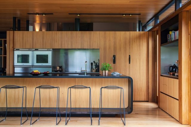 Hidden treasure: Herne Bay House |  Dorrington Atcheson Architects [Auckland, New Zealand]. This wooden kitchen features a beautiful 'floating' granite curved bench contrasting to the timber finishings of the rest of the cabinetry.