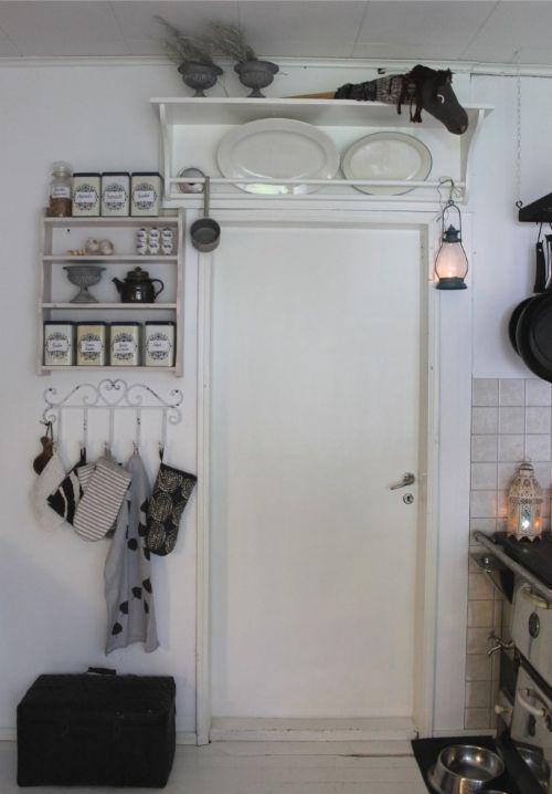 Rintamamiestalon keittiön nurkkaus. Vanha puuhella, valkoinen lautalattia ja persoonallisia esineitä. 50-luvun talo, maalaisromanttinen, sisustus