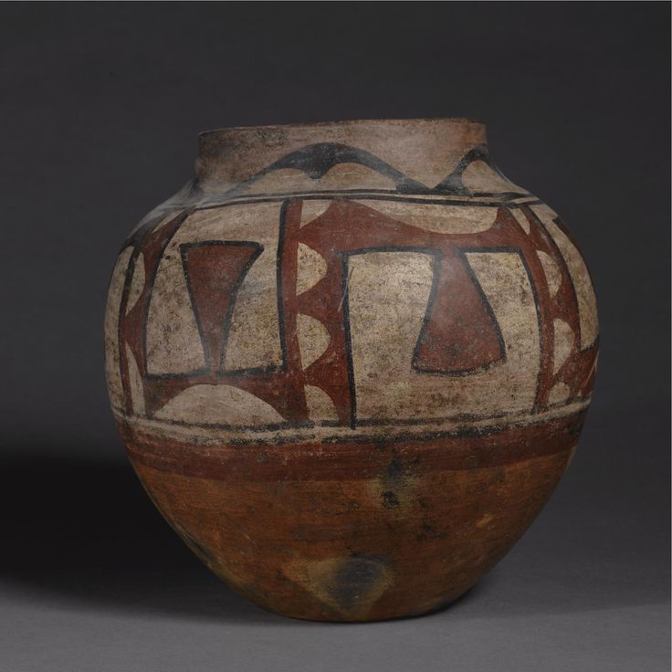 """Santa Ana Polychrome Jar circa 1830, with small concave base, tall rounded sides and short tapering neck, painted over a worn chalky tan slip in red and outline black, with a broad frieze of tapering and curving positive and """"negative"""" geometric elements, surmounted by a broad band of scalloped arches. height 9 7/8 in. by diameter 11 1/2 in. Sotheby's New York, November 1989, lot 81 Sotheby's. AMERICAN INDIAN ART 18 May 2007. NY."""