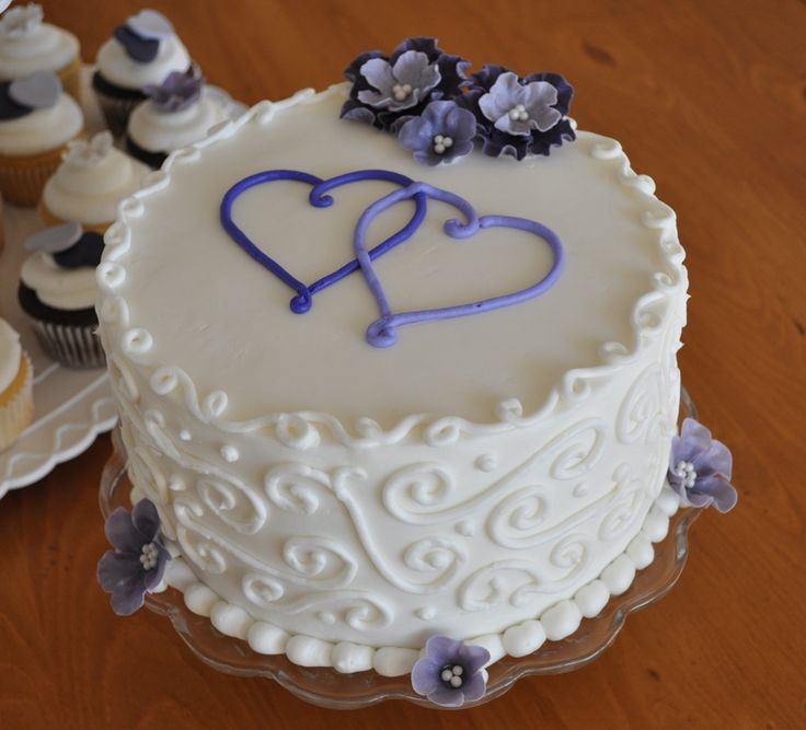 "8"" Round Wedding Cake with Double Purple Hearts - This cake is a small 8"" round, butter cream icing, scroll work and double hearts, with fondant flowers."