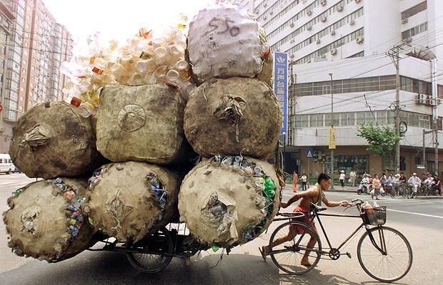 An enterprising man pulls a bicycle cart packed high with bags of recyclable plastic containers in Shanghai Picture: REUTERS