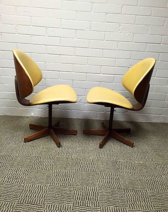 Pair of Mid Century Modern Kodawood Yellow Vinyl Swivel Desk Chairs from around 1960s. These chairs were manufactured by Kodawood of Miami. The chairs swivel really easy and would be excellent desk chairs. Both have a nice solid wood base. Extremely comfortable and in great vintage condition. There are no rips or tears in the vinyl and have normal vintage wear consistent with age.  Measures 31T x 20.5 W x 20D. From the floor to the bottom of the seat is 15.5  SHIPPING This item will ship…