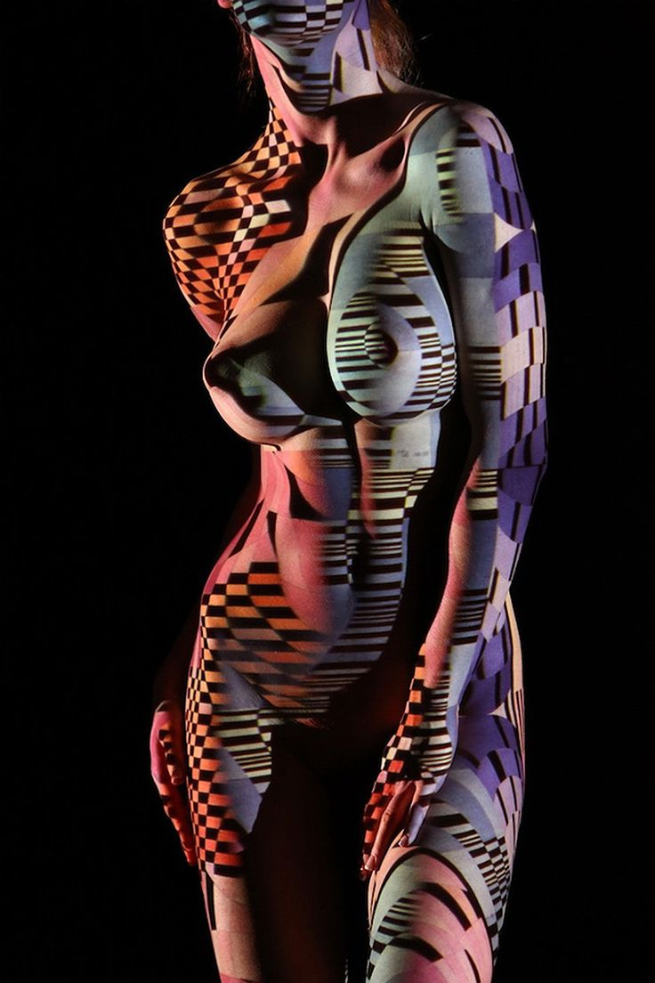 """To shoot these stunning nude portraits, Paris-based photographer Dani Olivier dressed his models with nothing but light, using their bodies as a canvas, combined with a series of geometric patterns to celebrate the beauty of the female form.  """"Dani Olivier began working with light projections some eight years ago, and he's been refining the process ever since. He prefers to collaborate with dancers and other women who move to the beat of their own drums, whose bodies can ripple through…"""