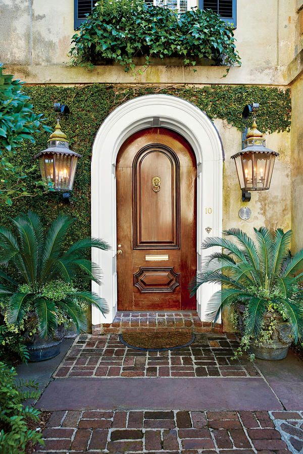 Tone-on-Tone - Front Door Container Gardens That Will Impress Guests - Southernliving. Visitors will marvel at this arched wood door and surrounding evergreen vines. To match the rounded door, we added large urns planted with sago palms.
