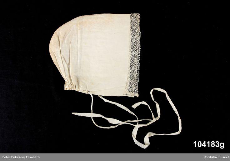 """Huvudliggaren: """"Dräkt för gift kvinna. 'Svartkjol', 'hvitförklä', 'svarttröja', 'sucko', halsduk, överdel, hatt, 'kläde' (huvudduk), hårband, skinntröja, handskar (halv d:o). Från Dalbyn.""""  Utdrag ur bilaga: """"388: Hvit fårkla. Ink af Anna Dalfors. Bäres till svart kjol vid sorg och i fastan (endast kyrkan). 387. Svartkjol, med blå framkant. Ink av hustrun Anna Dalfors. Nummerna 387 - 401 utgöra hel kvinnodräkt. 389. Svarttröja. Bars utanpå skinntröjan vintertid, på sommaren enbart…"""