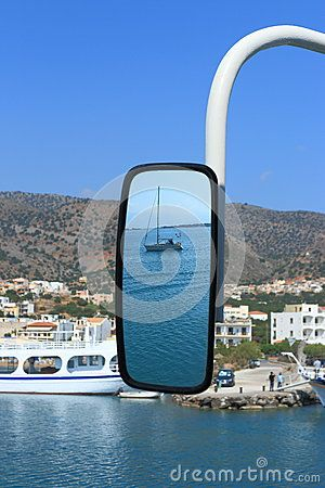 The reflection of yacht in the rear view mirror of a small cruise ship during boat trips on the Cretan sea. Crete, Greece