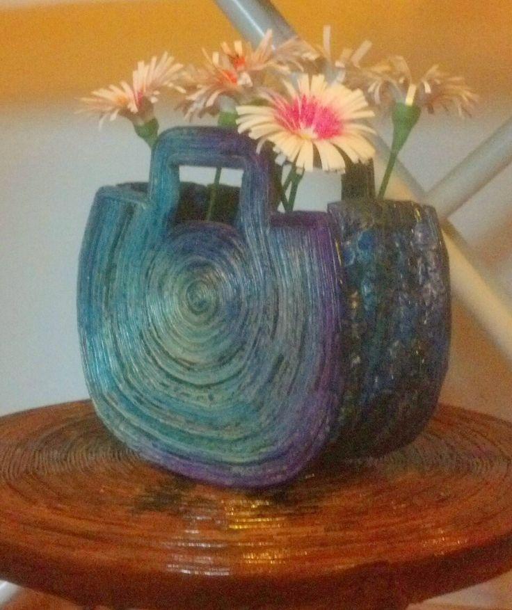 cesta de papel de periódico con flores de papel, en mesa de papel