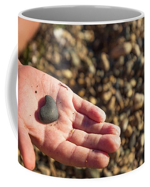 Mariia Kalinichenko Coffee Mug featuring the photograph Heart In A Child's Hand by Mariia Kalinichenko. Child happiness - find a stone in the shape of the heart.