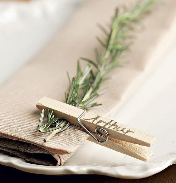 Marcadores de lugar feitos com um raminho de erva aromática, prendedor comum de madeira e caneta com tinta dourada.: