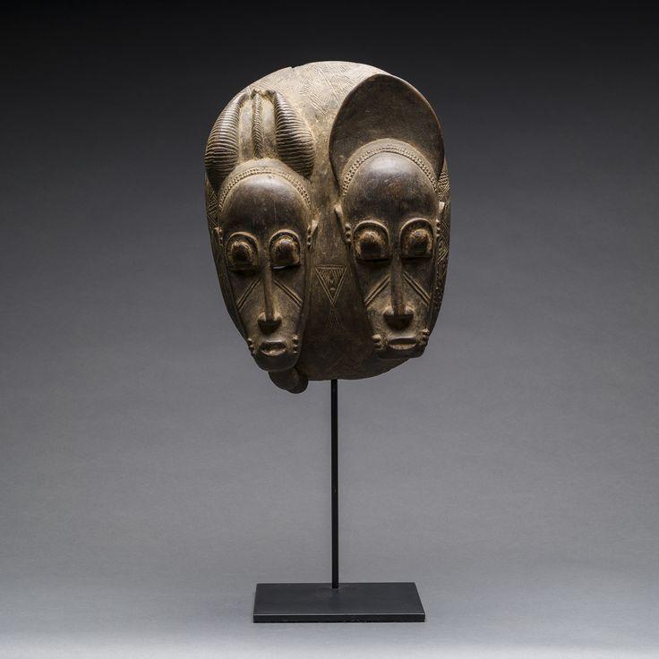 바울레족 쌍두 목제 마스크 Baule Bicephalous Wooden Mask, 1900AD, 아이보리코스트Ivory Coast, 목제Wood, Barakat Seoul _작품 설명_이 소형 목조 마스크는 아이보리 코스트 지역의 바울레족에서 제작한 작품입니다. 이 마스크는 피어싱을 한 마스크 형식으로, 특이하게도 머리 부위는 완전히 분리되어 있습니다. 얼굴은 남성 (왼쪽)과 여성 (오른쪽)으로 3 섹션으로 나뉘어져 있으며 수염의 여부에 따라 남성과 여성으로 구분됩니다. 얼굴의 일반적인 비율은 동일하지만 수염과 헤어 스타일에 대한 세부 사항은 약간 다릅니다. 여성을 묘사한 마스크는 나머지 두 인물에 비해서 약간 더 큽니다. 묘사된 인물들 양쪽에는 특이한 형태의 덮개가 장식되어 있고, 거꾸로된 T자와 같은 긴 코와 도톰한 입술, 동그란 두 눈을 가지고 있습니다. 인물들의 뺨에는 대각선 줄무늬가 장식되어 있습니다. (edited by Koo)
