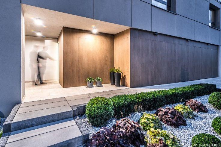 Wejście do domu. Ukryta brama garażowa.  Duża parterowa część budynku połączona z bryłą o dachu dwuspadowych od niedawna określaną jako nowoczesna stodoła. Duży taras, elewacja z płyt oraz tynku