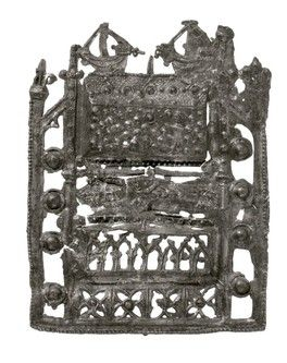 Pilgrim badge from the shrine of St Thomas Becket at Canterbury Cathedral. This openwork badge represents Becket's shrine itself. The base of the badge is decorated with cusped niches. Above this is a figure of Thomas Becket, lying down, his hands joined in prayer. He wears a mitre and archbishop's vestments. At the top of the badge is a gabled reliquary box which held Becket's bones. The reliquary is encrusted with jewels. Mid-late 14th century | Museum of London
