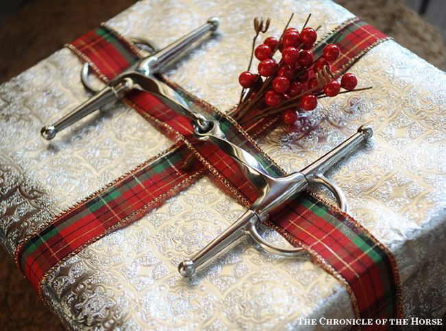 A snaffle bit, ribbon, and berries accent this equestrian present