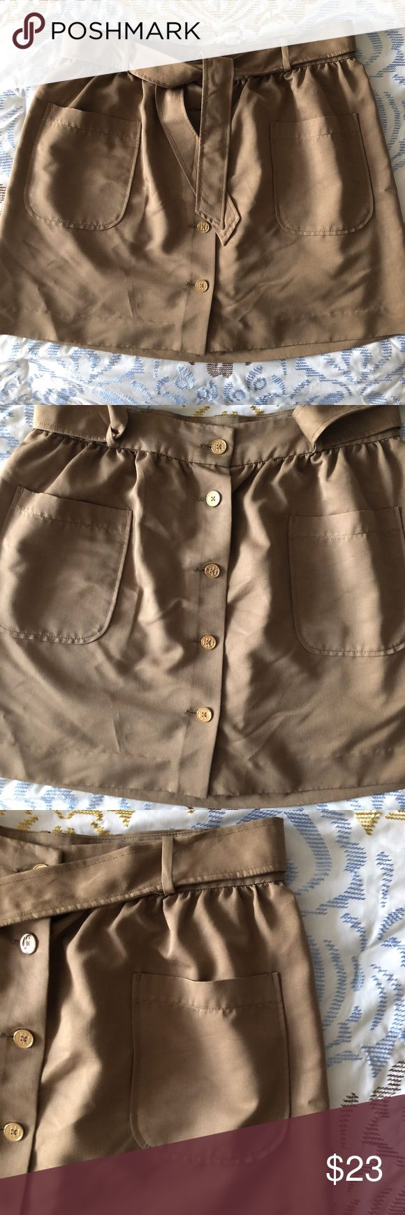 Tommy Hilfiger Button Front Tan Skirt Size 12 Tommy Hilfiger tan button up skirt in size 12. Gold buttons down the front with a belt and two front pockets. Lightweight cotton material, great for fall or spring! In excellent condition, no flaws. Tommy Hilfiger Skirts Mini