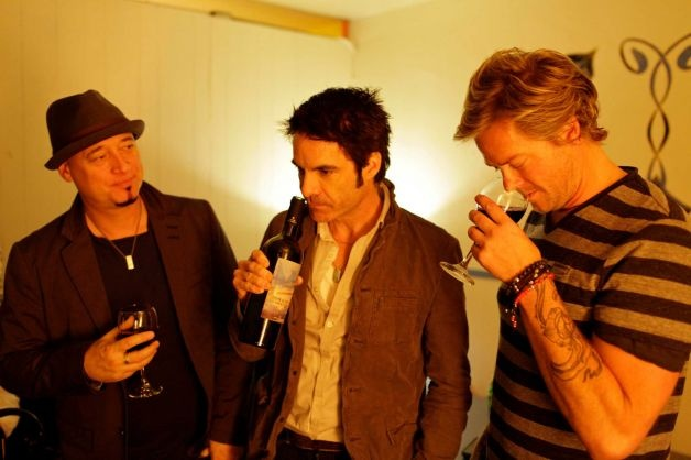 Jimmy Stafford, Patrick Monahan, and Scott Underwood of the band Train sample some of their wine before their concert at the Great American Music Hall in San Francisco