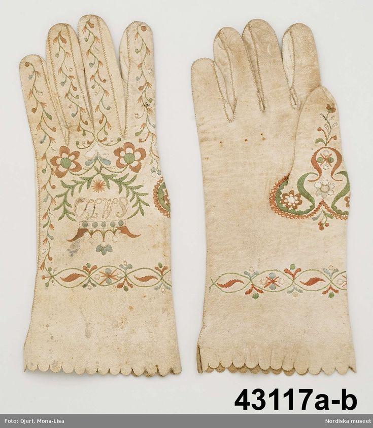 1 par handskar av vitt skinn med uddstansad kant.  På handens ovansida och på tummen  sirligt silkebroderi med blommor kring ett monogram med krona;