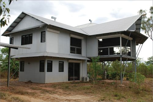 A two-storey home is supported by a ground floor for the main wing and by tall steel pylons for another wing. The house has a pitched roof with wide eaves, as well as a separate awning covering the lower storey.