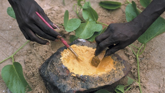 Making ochre by hand for a traditional Aboriginal painting.  Gove, Kakadu and Arnhem Land, Northern Territory, Australia