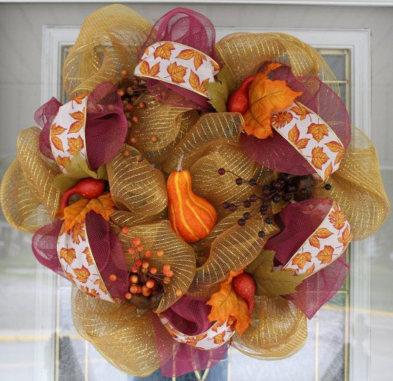 This homemade deco mesh wreath would look wonderful for Thanksgiving it is adorned with beautiful decorative squash in orange and yellow.  It's also has berry sprigs of 3 different colors dark brown, yellow, and orange.  The ribbon around the outside of the wreath has beautiful orange maple leaves with a red outline.